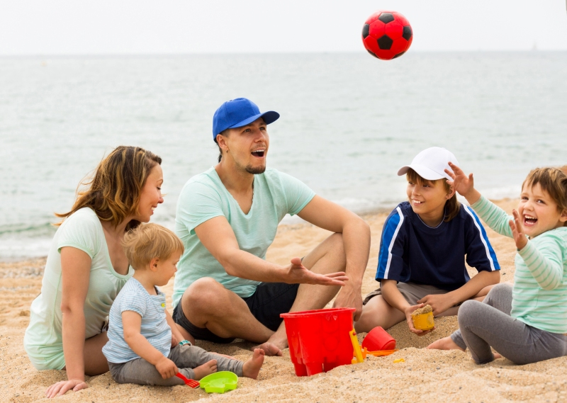 Happy family playing with ball at sandy beach